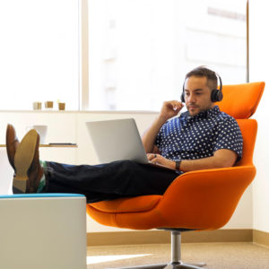 A man sitting on a comfy seat listening to headphones from his laptop