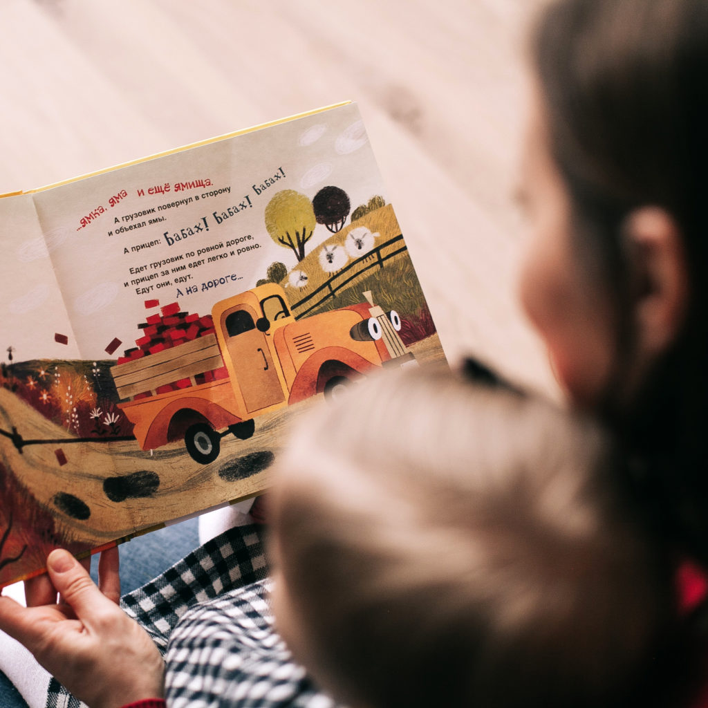 An adult reading a picture book to a child